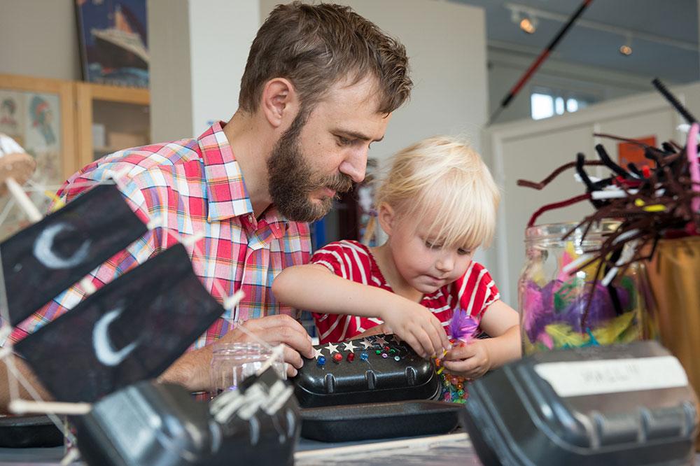 Ett barn och en vuxen pysslar tillsammans i Ruskpricken. De tittar koncentrerat på det de skapar, en båt av frigolit med paljetter ocg fjäder.